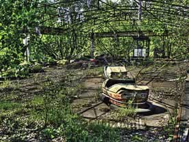 photo of a ruined amusement park, greenery overgrowing. Bumpercar in foreground