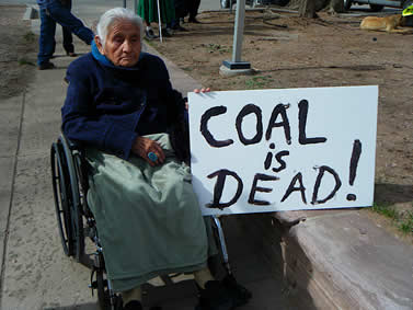Photo of a woman in a wheelchair holding a sign that reads, coal is dead
