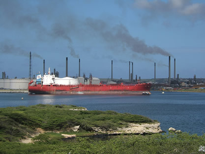 photo of a waterside refinery, giant tanks and ships