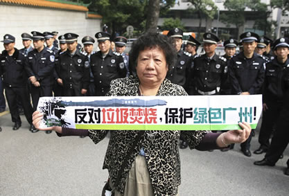 photo of a serious-looking woman holding a banner, behind her are dozens of uniformed police