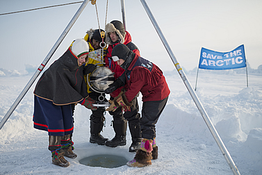 photo of warmly-clad folks on an ice floe, lowering a container into a hole leading to the sea. a banner in the background reads, save the arctic