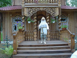 photo of a man dressed in a Father Christmas costume standing before an elaborately carved wooden structure