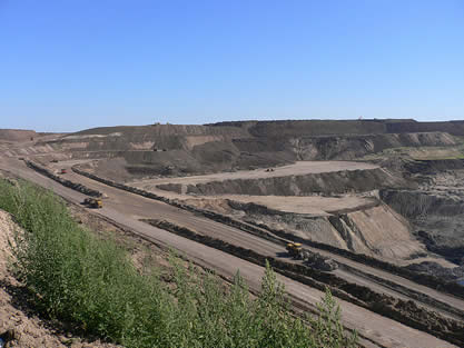 photo of a barren, carved landscape, mining equipment visible