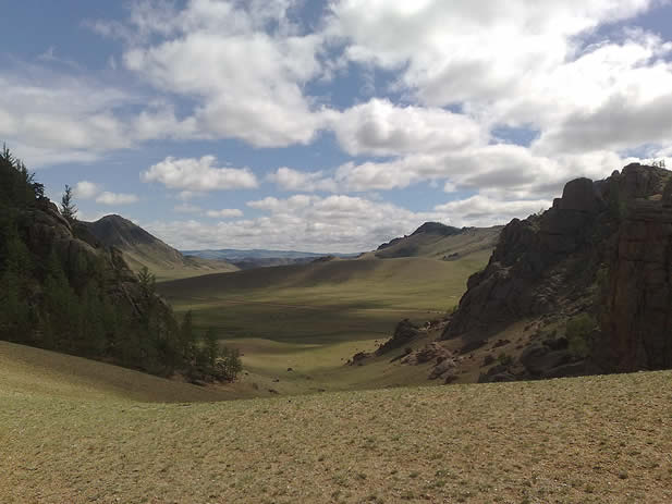 photo of a valley under a wide sky, rock formations and sparse tree cover apparent; no sign of habitation