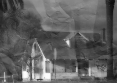 antiqued photo of an abandoned home, palm trees and a crucifix in the yard, graffiti on the boarded up windows