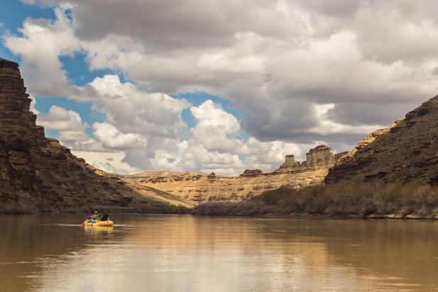 photo depicting rafts on a desert river canyon