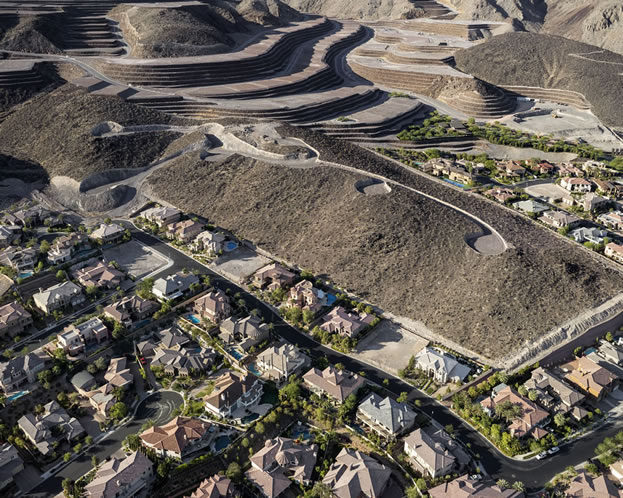 aerial photo of large homes abutting a hillside covered with graded empty lots