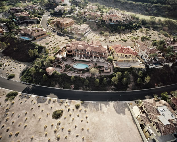 aerial photo of mansions with swimming pools in a desert, many look unoccupied