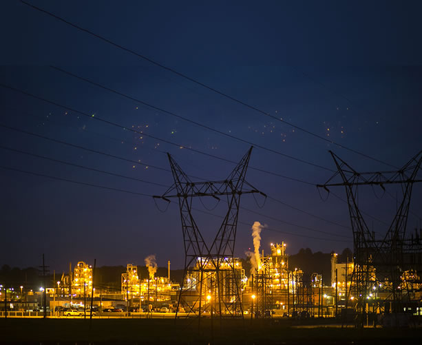 photo of a well-lit chemical factory at night
