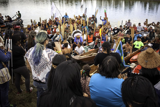 photo of a crowd on the shore of a lake, paddles and watercraft evident