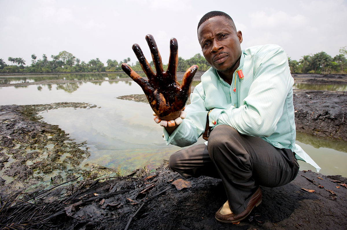 Eric Dooh shows how crude oil coats the banks of a creek that runs through his village, Goi. Several leaks in a Shell pipeline in the 2000s polluted the creek and other water bodies in the village, killing all aquatic life and ultimately forcing villagers to abandon Goi. Photo Marten van Dijl / Milieudefensie