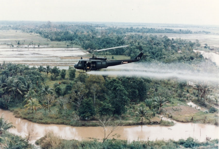 U.S. Army Huey helicopter spraying Agent Orange over agricultural land during the Vietnam War in its herbicidal warfare campaign. Photo US Army.