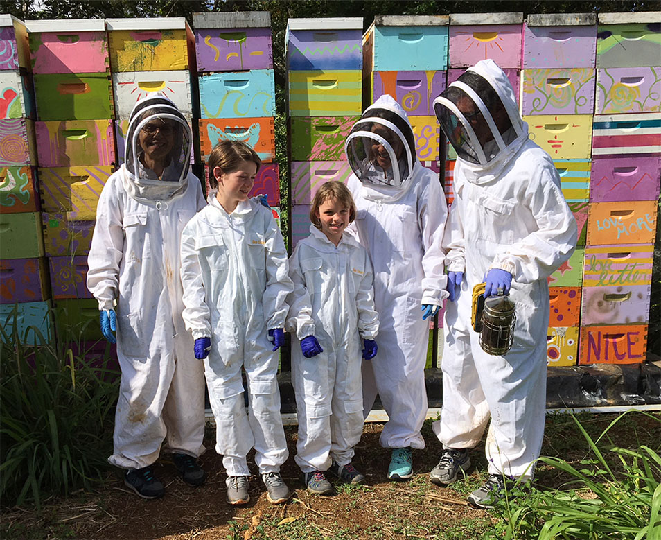 The author and her family during a visit to some of Robin Fisher's bee hives on a farm on the Hawaiian island of Kauaʻi.