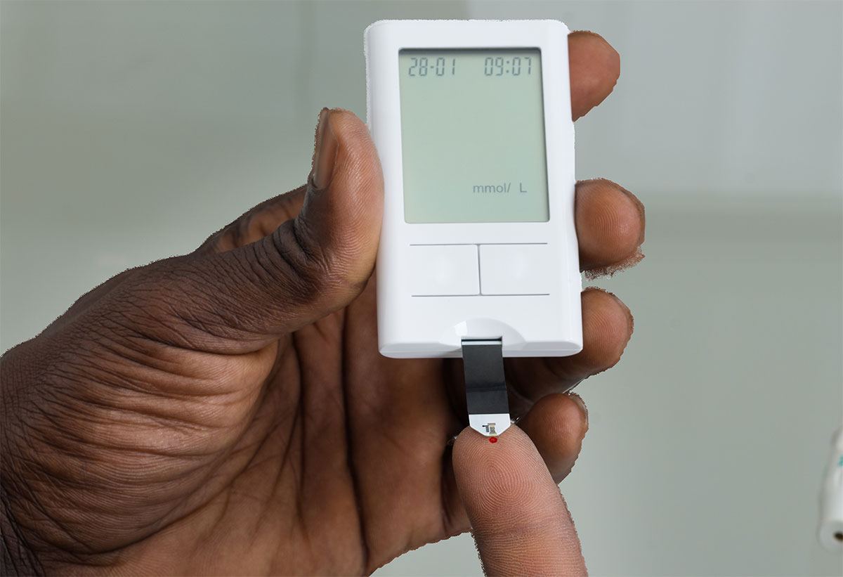 hand with glucometer