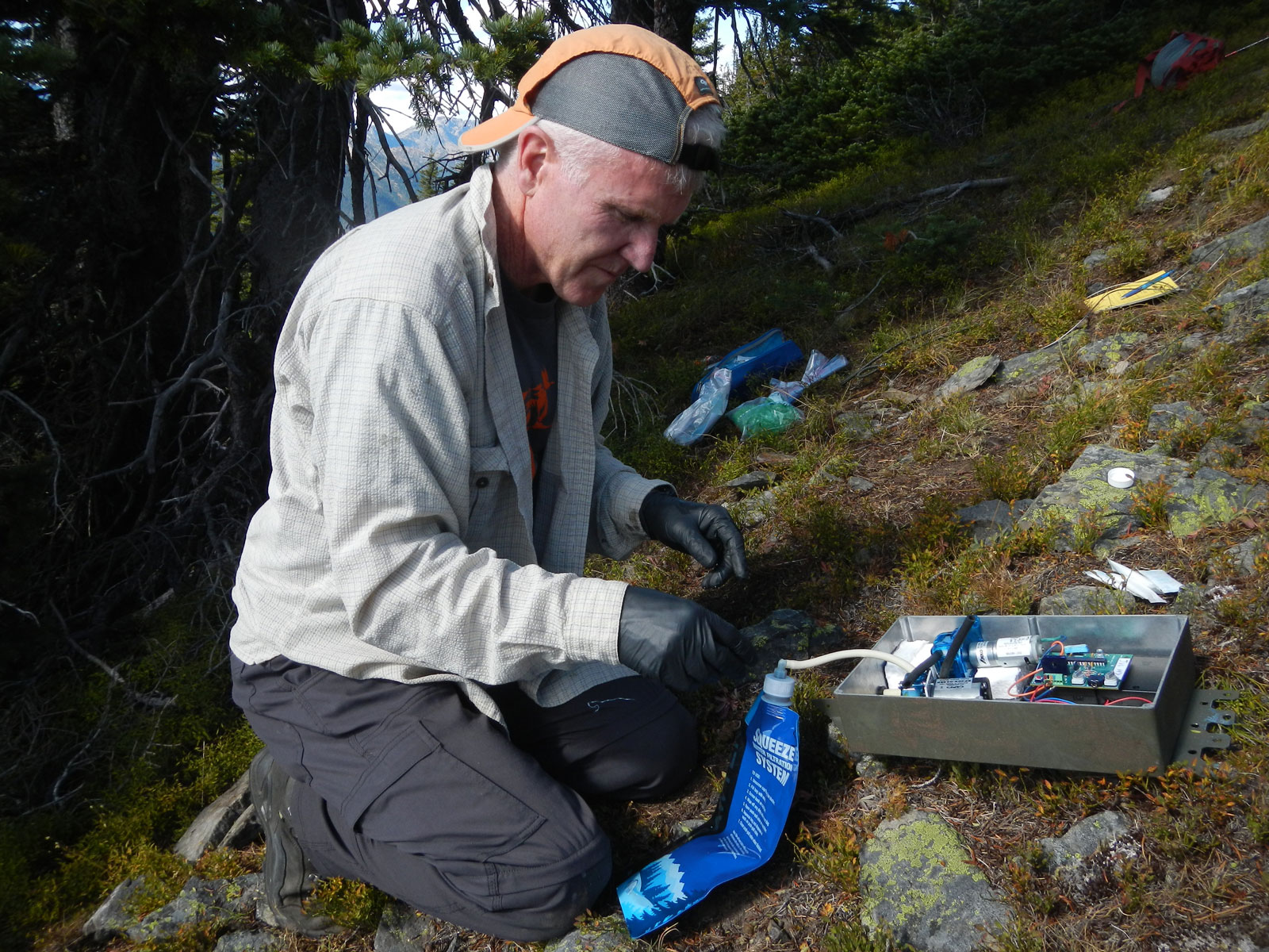 Robert long prepares an automated scent dispenser to attract wolverines during the winter months when the Cascades are hard for researchers to access. The dispenser will be hung high in a tree above the snow line. Photo by Paula MacKay.