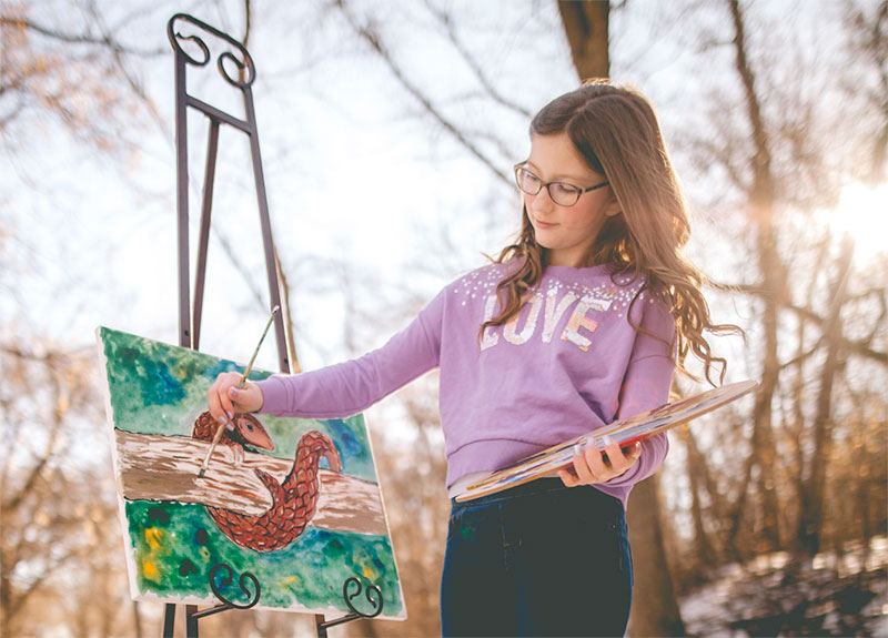photo of a young woman painting at an easel outdoors