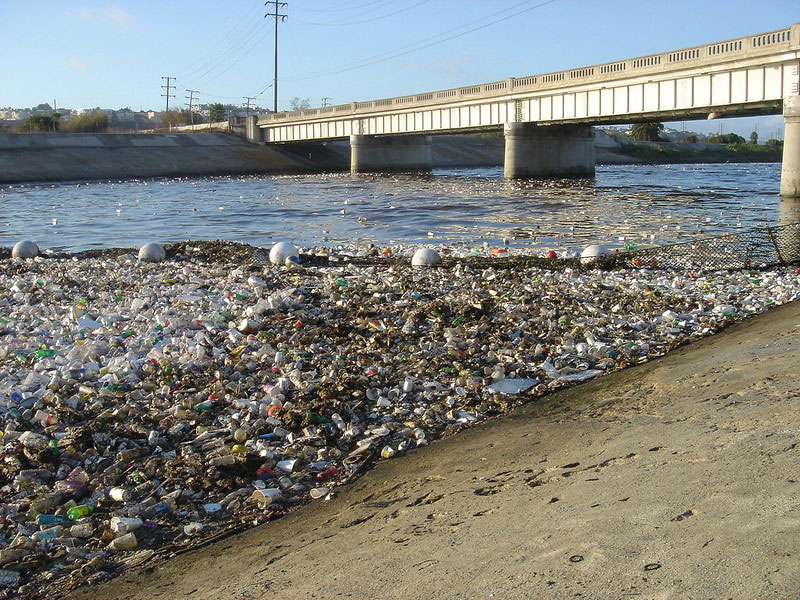 photo of a shoreline buried in plastic waste