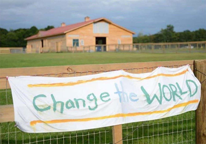 photo of a banner on a fence, words, change the world