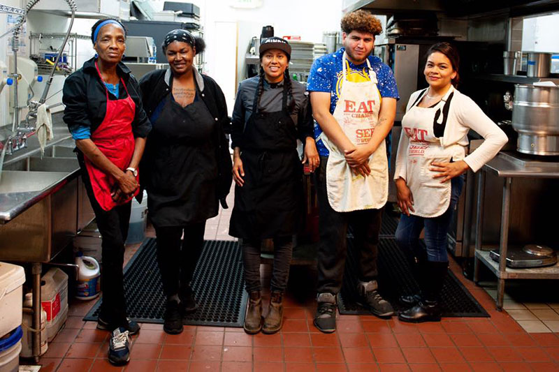 photo of a group of people working in a kitchen