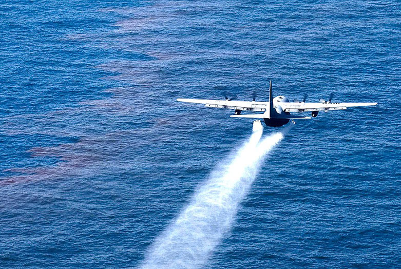photo of plane flying over the sea, spraying something